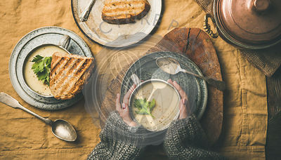 Celery cream soup, grilled bread and female hands