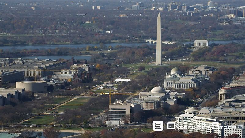 Wide view of the National Mall from Capitol Building to Lincoln Memorial. Airplane flies from right to left behind Washington Monument. Shot in November