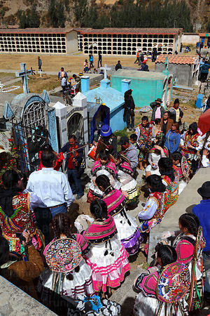 Dance group and musicians at grave of deceased relatives in cemetery , Virgen del Carmen festival , Paucartambo , Peru