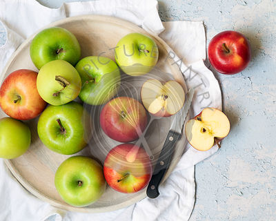 Green and red apples with two apple halves and knife on a round wooden serving board.