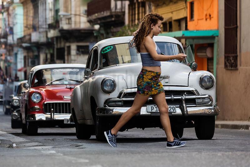 Woman Crossing Road in Front of Vintage American Cars