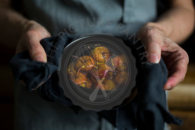Close-up of man's hands holding cocotte with stuffed roast apples in his hands