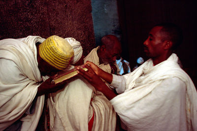 Ethiopia - Lalibela - Monks kissing a bible at a dawn service