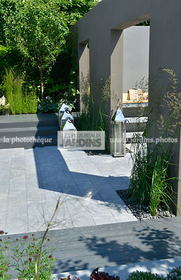 Jardin urbain, style contemporain : Dallage en pierre venant d'Irlande. Décoration au jardin : Photophore. Paysagiste : Paul Martin, Hampton Court, Angleterre