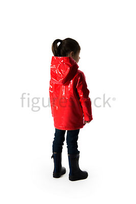 A little girl in wellies and a red raincoat standing and looking away – shot from mid level.