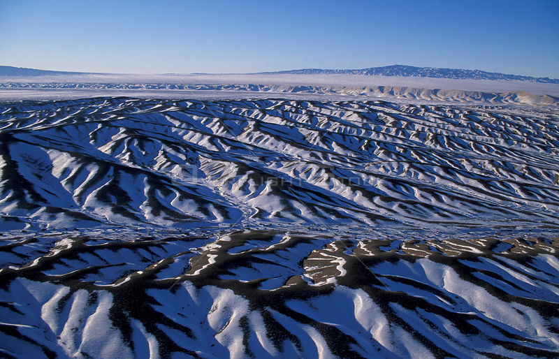 Aerial view of abstract dune patterns with snow, Gobi Desert, Mongolia, January 2004..Filmed for BBC Planet Earth series.