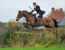 John Knowles jumping a hedge from the meet