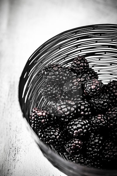 Organic ripe blackberries in a black wire bowl on a white wooden surface.