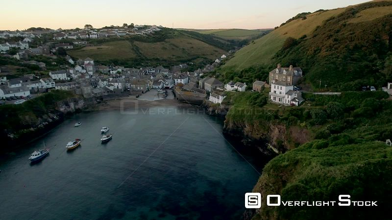 Drone flies sideways over harbor of Port Isaac in Cornwall. Shot during the dawn twilight.