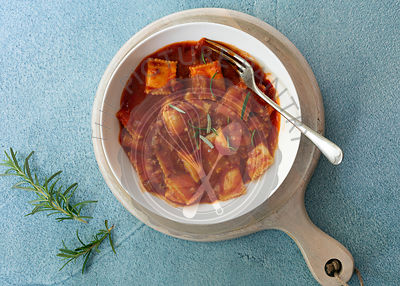 A bowl of ravioli in tomato and meat sauce with a fork on wooden serving board.