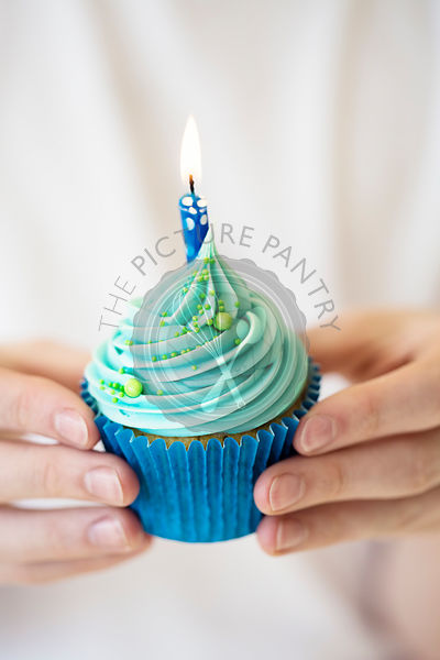 Hands holding birthday cupcake