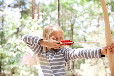 Girl shooting with bow and arrow in the forest