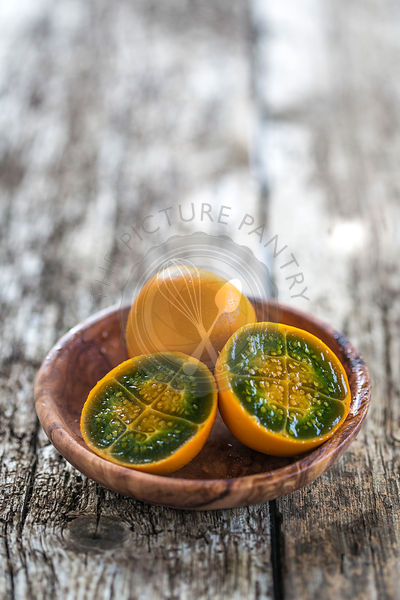 cut vibrant green and orange fleshed naranjilla in a wood bowl on rustic wood table
