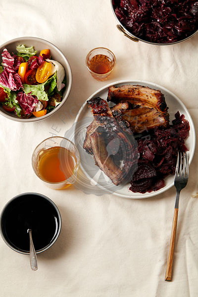 Main dish with grilled pork ribs in thick barbeque sauce garnished with red cabbage and beets