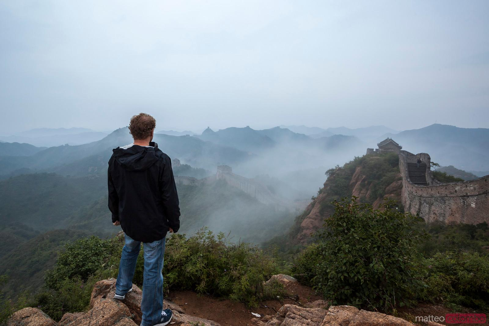 Tourist looking at the Great Wall in a misty morning
