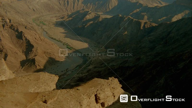 Aerial wide angle shot top and sides of mountains with river and riverbanks below, river curves right Fish River Canyon Namibia