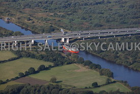 Manchester Ship Canal aerial photograph of the Happy Falcon navigating the Manchester Ship Canal about to pass under the M6 motorway Thelwall viaduct