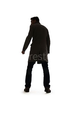 A silhouette of a mystery man in a coat, looking around – shot from low level.