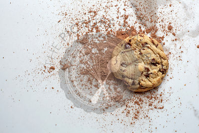 Single chocolate chip cookie on a white marble table with cocoa powder