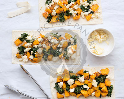 Three uncooked roast pumpkin, spinach and feta cheese tarts with open tongs on baking paper.