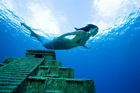Mermaid diving near Mayan Temple replica underwater off west side of Cozumel, Mexico.