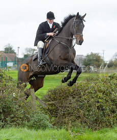 Tom Abel Smith jumping a hedge near the meet in Long Clawson