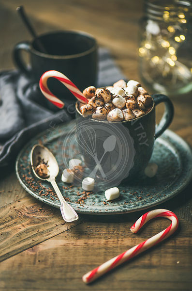 Winter warming sweet drink hot chocolate with marshmallows and cocoa in mug with Christmas holiday candy cane