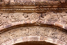 Detail of carvings of angels and christogram above main side entrance of St John the Baptist of Letrán / San Juan Bautista de Letrán church, Juli, Puno Region, Peru