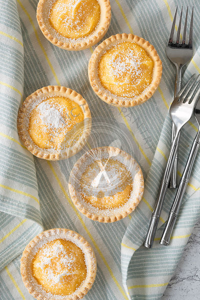 Five lemon tartlets dusted with powdered sugar.