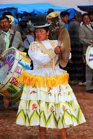Cholita playing clash cymbals in brass band at festival in Caquiaviri, Bolivia