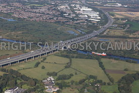 Manchester Ship Canal aerial photograph of the Happy Falcon navigating the Manchester Ship Canal about to pass under the M6 motorway Thelwall viaduct with the nature reserve in the distance