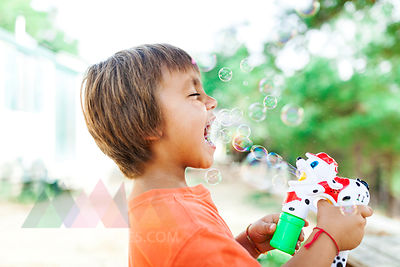 Little boy playing with soap bubble machine