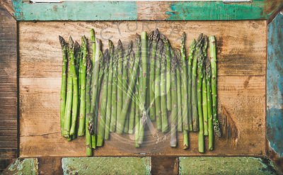 Raw uncooked green asparagus in row over wooden tray background