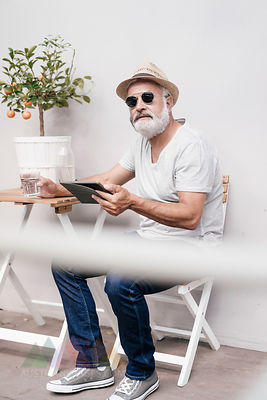 Mature man wearing straw hat holding tablet next to table with orange tree