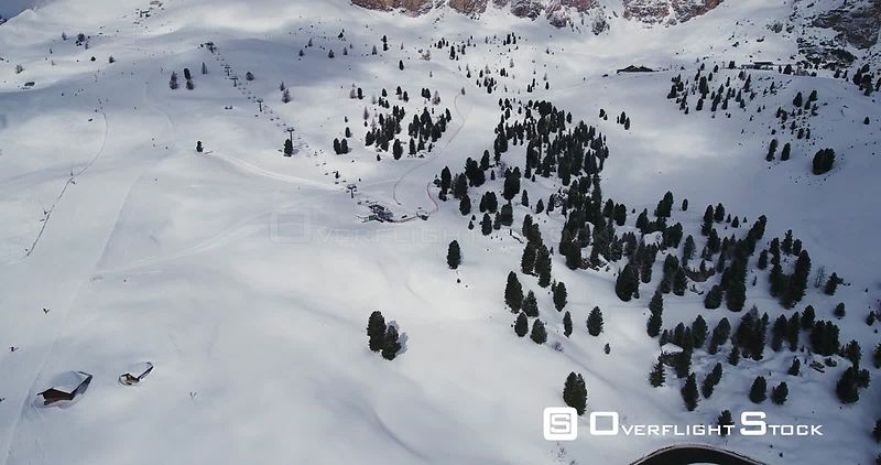 Aerial, breathtaking snowy mountains, ski tracks in winter Alps in Italy
