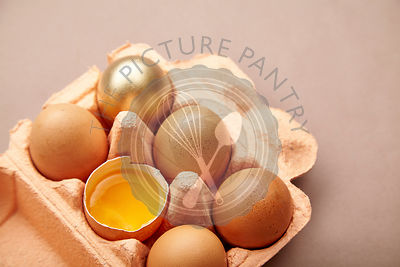 Half Dozen of chicken eggs in colorful cardboard container with one golden egg