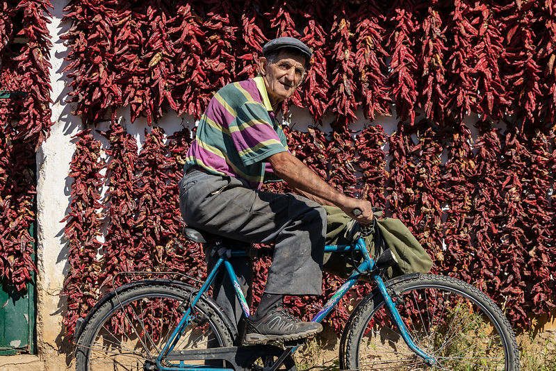 Villager on a Bicycle in Front of Drying Peppers