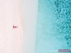 Woman relaxing on beach, aerial view, Maldives