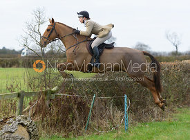 Sophie Pedlar jumping a hedge near the meet - The Belvoir Hunt at The Wolds Farm 3/12