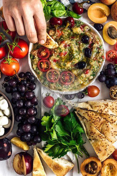 Eggplant babaganoush with red bell pepper and herbs on a snack board full of summer fruit photographed from top view. A woman is dipping a bread into it.