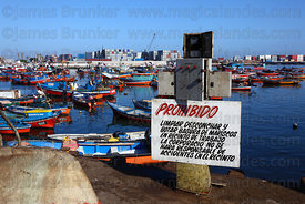 Sign telling fishermen not to clean and throw away shellfish on quay in port , Iquique , Chile
