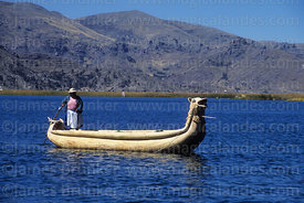 Aymara woman steering totora reed boat between Uros floating islands , Lake Titicaca , Peru