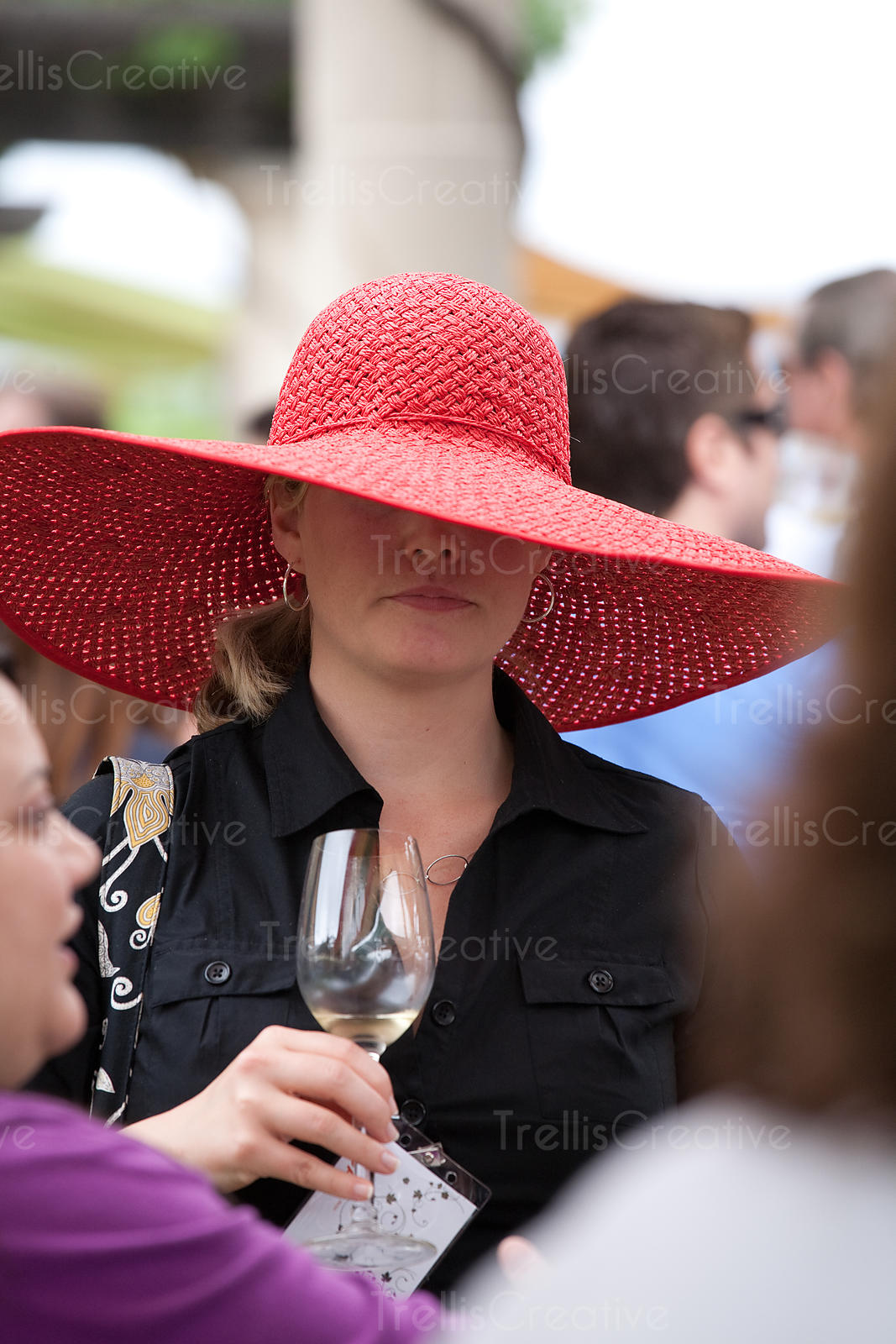 Young woman wearing a big Kentucky Derby style hat while drinking a glass of white wine