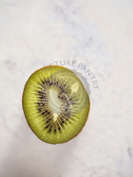 Half kiwi showing detail of flesh and seeds on a bright, white, textured surface.