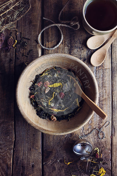 Herbal dry tea leaves with wild flowers and dried fruit on wooden rustic table. Top view