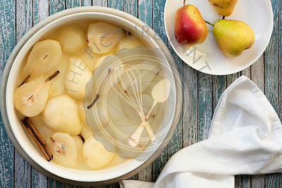 A bowl of poached pears and a cinnamon stick in syrup beside three uncooked red pears.