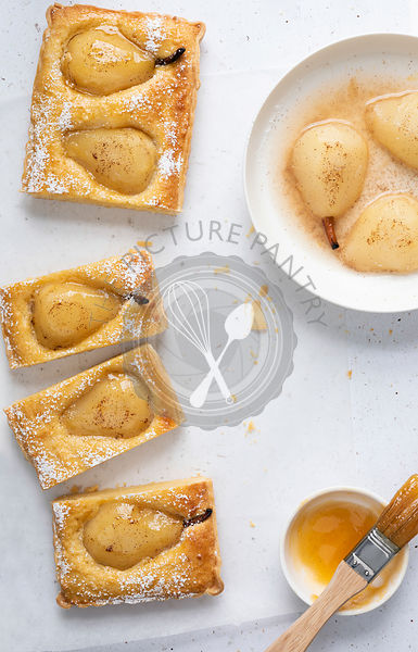 Glazed pear tart cut into pieces with a bowl of pear halves and a bowl of glaze.
