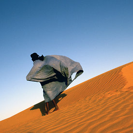 A man walks over a dune overlooking Chinguetti, Mauritania.