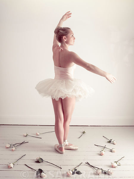 Young Ballerina dancing with roses on floor