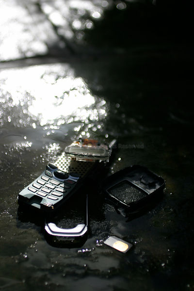 Broken mobile phone on rain soaked path